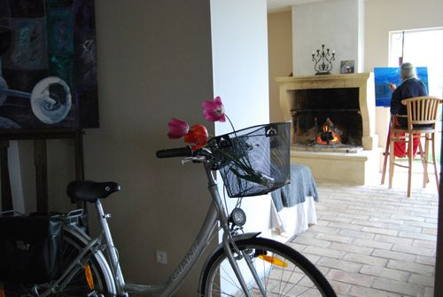 bike with basket, stone fireplace, old floor tiles, painting , france, candelabra (c) Kristin Espinasse, french-word-a-day.com