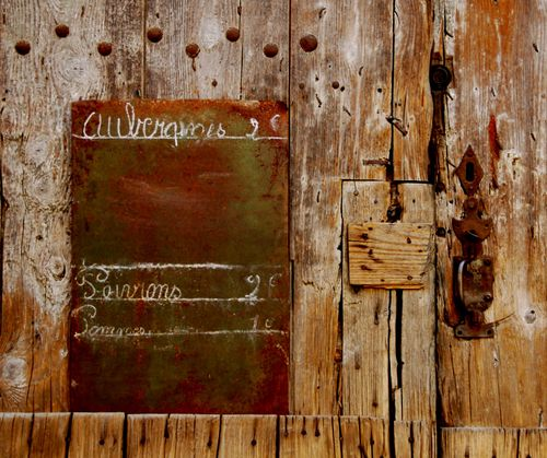 Old French sign, handwritten, chalkboard, wooden door, eggplant, peppers, aubergines (c) Kristin Espinasse, french-word-a-day.com