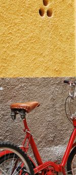 red bicycle, yellow wall (c) Kristin Espinasse, french-word-a-day.com