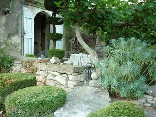 stone cottage and window shutters on shaded patio in Provence. Manicured garden with euphorbia and pruned hedges (c) Ann Mah for www.french-word-a-day.com