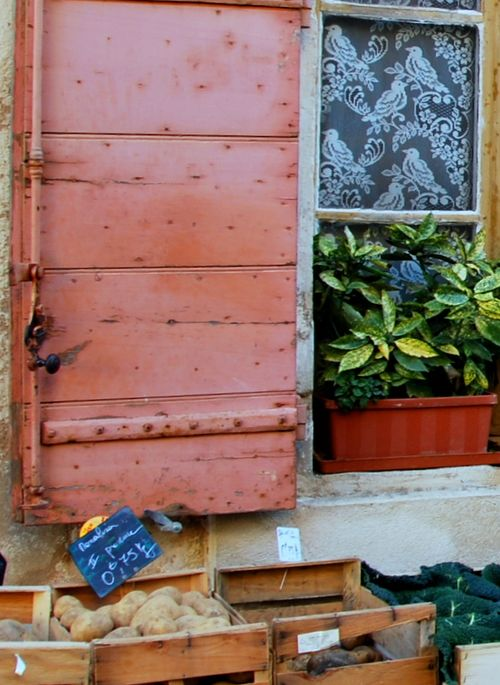 Lace curtains at the produce stand in Roquemaure, France (c) Kristin Espinasse