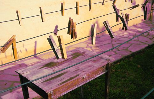 Clothesline and pegs, or clothespins. Old weathered desk, flagstone (c) Kristin Espinasse, www.french-word-a-day.com