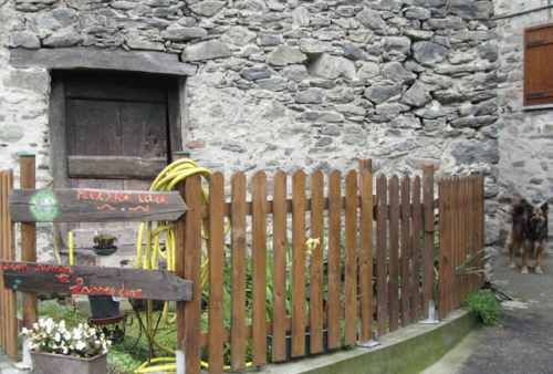 stone house yellow hose painted sign dog picket fence wooden lintel italy aosta valley dog Love Well (c) Kristin Espinasse