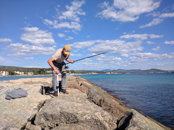 Setting up his fishing pole canne a peche in the digue sea wall france la ciotat