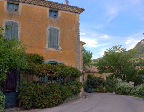 yellow bastide rhone france provence vines trellis shutters iron gate mountain